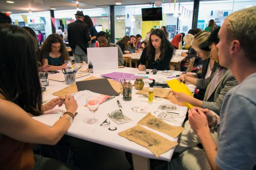Students taking part in an Illustration workshop around a table