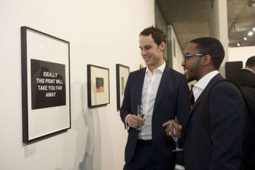 Two men looking at artwork hung on the wall of the gallery