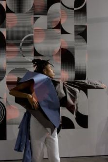 Photograph of someone performing, wearing a garmet with a large protrusion over the shoulder, stood infront of an abstract geometric pattern on the wall