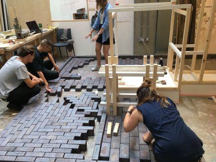 People arranging bricks in pattern on floor