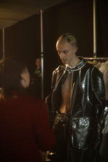 Male model in perspex jacket being dressed