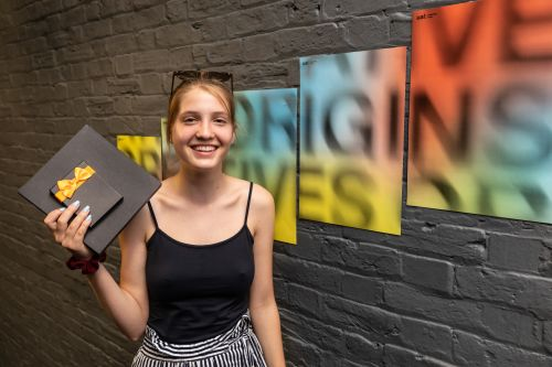 A student prize winner poses with their prize