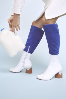 Image of white leather heeled boots worn with colbalt blue trousers and matching white hand bag