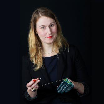 Portrait photograph of tutor, Riina Õun, working on a glove.