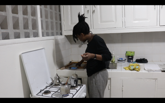 woman standing at an oven making paper