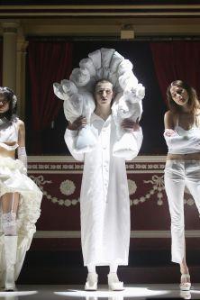 Models wearing white garments standing on catwalk