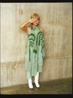 A model in Emily's fashion design of a long green shirt dress.