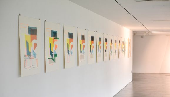 Multiple replicas of the same drawing hung up on a gallery wall in a row