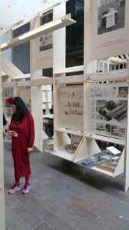 A woman wearing red stood in front of a large structure which is exhibiting a series of architectural sketches