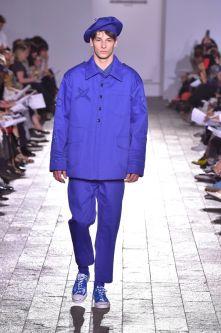 A model walking down a catwalk wearing a purple suit and a purple beret