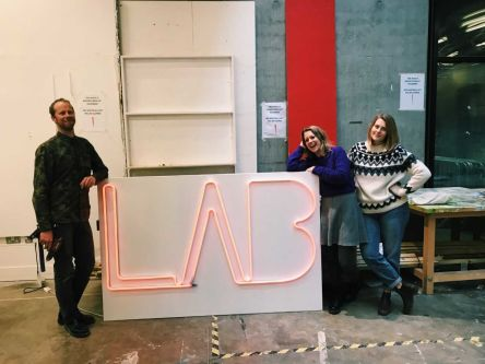 Three people stood next to a neon light that reads 'LAB',