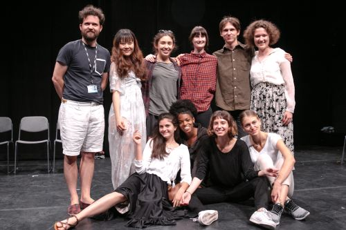 Group of Theatre students standing together on stage, smiling at camera