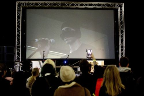 A photograph of a crowd from behind, watching someone perform on stage, a large screen behind showing a man with his mouth and nose covered by a mask