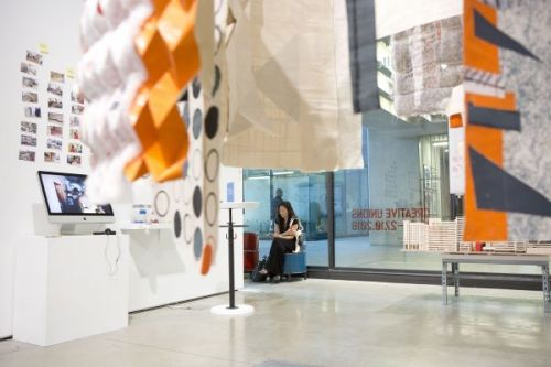 Photograph of the exhibition in the gallery of someone looking at work
