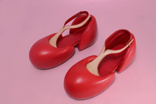 Red shoes with nude t bar on pink background
