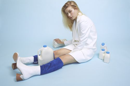 Female model in white coat with blue socks and white boots