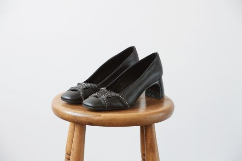 Black heeled mules resting on a wooden stool
