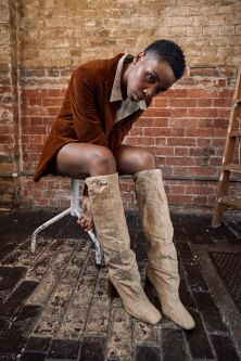 Model wearing tan jacket modelling knee high leather beige boots