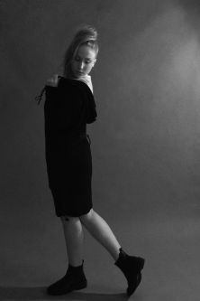 Model in black shirt dress posing with back to the camera in black and white backdrop