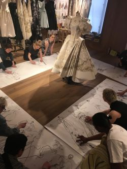 People sitting sketching around dress on stand
