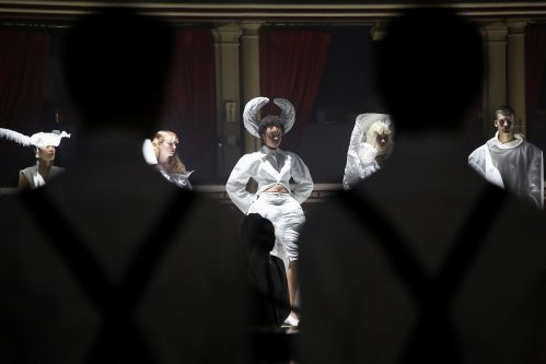Models wearing white garments walking along catwalk