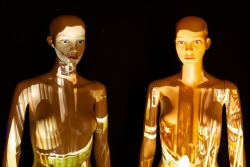 two mannequins with light projections covering them.