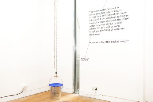 Installation showing a metal bucket filled with solid blue material, representing the weight carried by a single child.