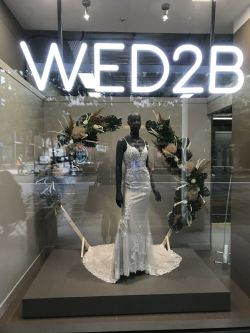 A photo of a mannequin wearing a long white dress in the window of a shop called WED2B.