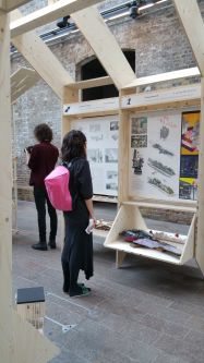 A person which a bright pink backpack is looking at work by BA Architecture students
