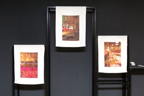 Image of black frame with three prints hanging off the structure
