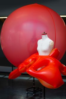 A large red inflated balloon next to a mannequin wearing a garment made from a red balloon