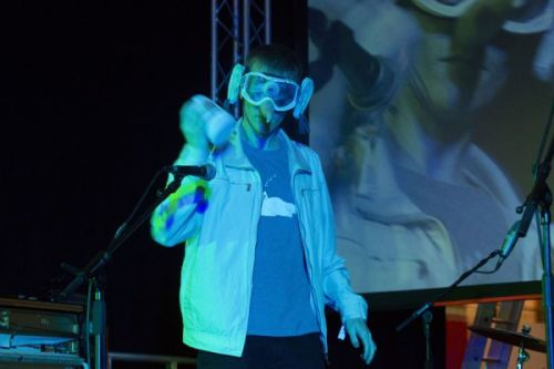 A photograph of a man on a stage under heavy blue lighting, wearing large goggles and shaking something in one hand