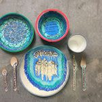 Photograph of several bowls and plates decorated with blue and teal patterns and writing