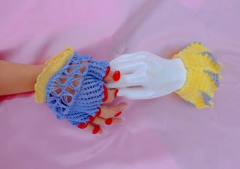 Knitted gloved hand holding a mannequin's hand