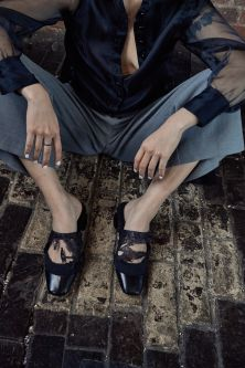 Cropped shot of feet and hands modeling black mules