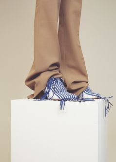 Tan baggy trousers worn with mid heel white and blue striped pointed shoe