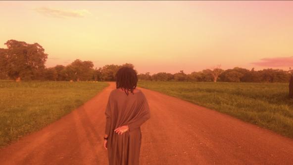 woman walking down dirt path - bright orange filter