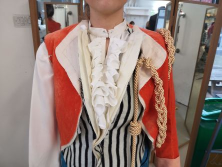 Photo of a partially made red velvet jacket, worn over a horizontal-striped waistcoat, with gold rope details.