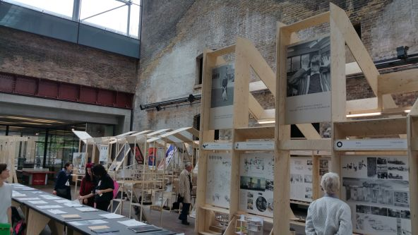 People looking at architecture projects and sketches which are on display on a long black table and on wooden structures