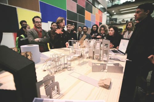 A crowd of people are stood around a table which is displaying a series of architectural models