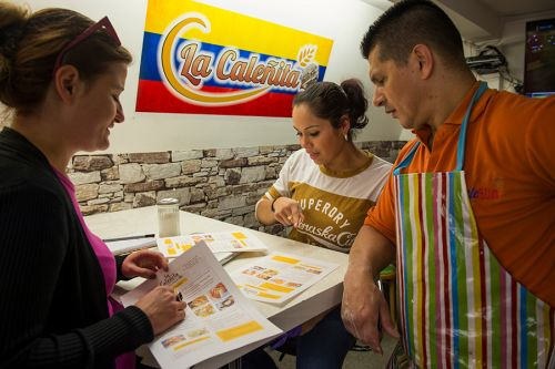Designer Stanislava shows La Caleñita bakery owners, Oscar and Valeria, different options for their menu.