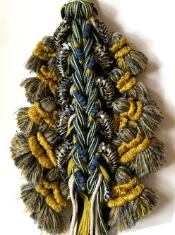 A row of tassels and fringing in gold, yellow, blue and green materials