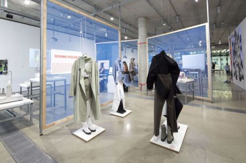 Photograph of the gallery with three mannequins displaying garments