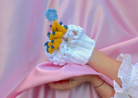 Knitted gloved hand holding a knitted flower