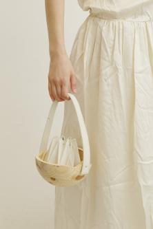 Model holding white wooden bag