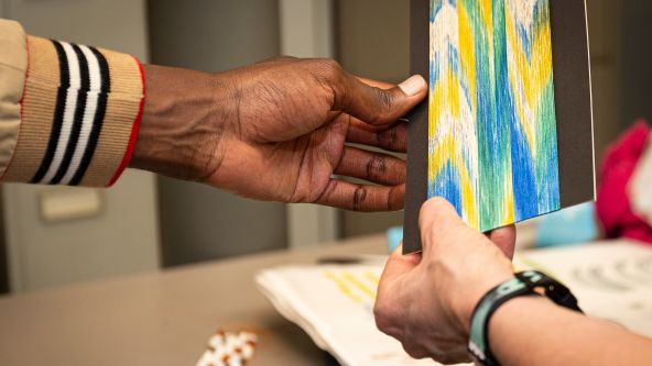 Close up of hands - Swarovski staff member examining a textiles student's work at the portfolio viewing