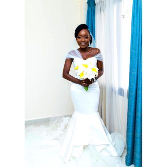 Woman wearing white wedding dress, designed by Tope