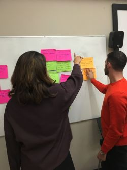 Students putting post-it notes on the white board
