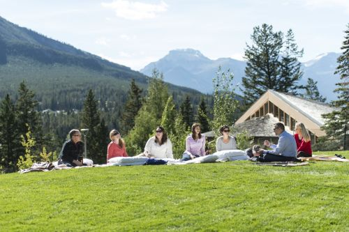 Landscape image of mountains in canada with people sat on grass verge