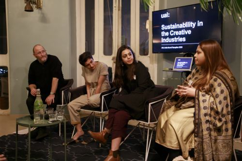 Photo of four people on a panel, sat in front of a screen which says 'UAL: Sustainability in the Creative Industries'